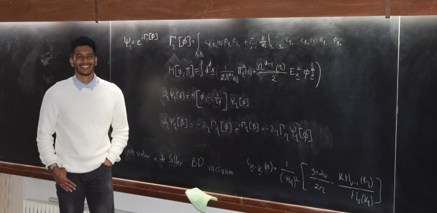 Ayngaran Thavanesan standing in front of a black board filled with equations.