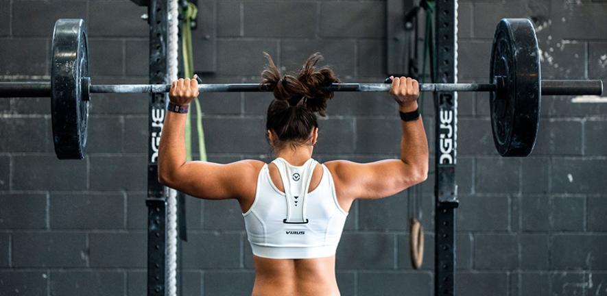 Woman lifting weights. Credit: John Arano on Unsplash